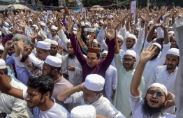 Islamist activists shout slogans as they take part in a protest in Dhaka on October 21, 2019, a day after deadly clashes when police shot at Bangladeshi Muslims protesting Facebook messages that allegedly defamed the Prophet Mohammed. - Bangladesh police on October 21 was investigating up to 5,000 people for taking part in one of the nation's deadliest religious riots where at least four were killed when officers fired on protesters. (Photo by Munir UZ ZAMAN / AFP)