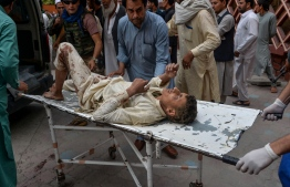 """Volunteers carry an injured man on a stretcher to a hospital, following a bomb blast in Haska Mina district of Nangarhar Province on October 18, 2019. - At least 62 people were killed by a blast inside an Afghan mosque during Friday prayers on October 18, according to officials, a day after the United Nations said violence in the country had reached """"unacceptable"""" levels. (Photo by NOORULLAH SHIRZADA / AFP)"""