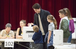 Leader of the Liberal Party of Canada, Justin Trudeau votes with his family in Montreal, Quebec on  October 21, 2019. - Canadians began voting in a general election Monday, with surveys predicting a minority government as Prime Minister Justin Trudeau's Liberal Party risks losing its majority or even being kicked out of office.The Liberals and the Conservatives, led by Andrew Scheer, could be set for a near dead heat with pundits calling it one Canada's closest elections ever. (Photo by Sebastien ST-JEAN / AFP)