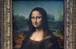 """(FILES) This file photograph taken on October 7, 2019, shows The Mona Lisa (La Gioconda) after it was returned to its place at the Louvre Museum in Paris. - The Louvre in Paris is putting the finishing touches to an ambitious Leonardo da Vinci retrospective opening on October 24, 2019, which groups more than 160 of the artist's works and has already attracted close to 200,000 advance visitor bookings. Timed to coincide with the 500th anniversary of the famed artist's death, the show, simply called """"Leonardo da Vinci"""", took a decade to put together and includes works on loan from Queen Elizabeth and Bill Gates. (Photo by ERIC FEFERBERG / AFP) /"""