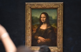 """(FILES) In this file photograph taken on October 7, 2019, visitors take photographs in front of The Mona Lisa (La Gioconda) after it was returned to its place at the Louvre Museum in Paris. - The Louvre in Paris is putting the finishing touches to an ambitious Leonardo da Vinci retrospective opening on October 24, 2019, which groups more than 160 of the artist's works and has already attracted close to 200,000 advance visitor bookings. Timed to coincide with the 500th anniversary of the famed artist's death, the show, simply called """"Leonardo da Vinci"""", took a decade to put together and includes works on loan from Queen Elizabeth and Bill Gates. (Photo by ERIC FEFERBERG / AFP) /"""