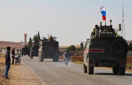 A convoy of Russian military vehicles drives toward the northeastern Syrian city of Kobane on October 23, 2019. - Russian forces in Syria headed for the border with Turkey today to ensure Kurdish fighters pull back after a deal between Moscow and Ankara wrested control of the Kurds' entire heartland. (Photo by - / AFP)