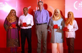 Bank of Maldives (BML) CEO and MD Tim Sawyer posing for a picture for employees that served the bank for 30 years. PHOTO: BML