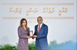 A family member accepts the National Award of Honour conferred posthumously on the late Sayyid Hassan, for his contributions in the area of sports in sportsmanship and sports development. PHOTO: HUSSAIN WAHEED / MIHAARU