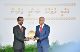 A family member accepts the National Award of Honour conferred posthumously on the late Dr Afrasheem Ali, for his contributions towards Islamic awareness and Islamic education. PHOTO: HUSSAIN WAHEED / MIHAARU