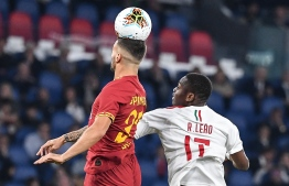 AS Roma's Italian defender Leonardo Spinazzola (L) jumps for the ball with AC Milan's Portuguese forward Rafael Leao, during the Italian Serie A football match between AS Roma and AC Milan, on October 27, 2019 at the Olympic stadium in Rome. (Photo by Andreas SOLARO / AFP)