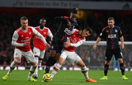 Crystal Palace's Ivorian striker Wilfried Zaha (C) vies with Arsenal's Swiss midfielder Granit Xhaka (2nd R) during the English Premier League football match between Arsenal and Crystal Palace at the Emirates Stadium in London on October 27, 2019. (Photo by DANIEL LEAL-OLIVAS / AFP) / RESTRICTED TO EDITORIAL USE. No use with unauthorized audio, video, data, fixture lists, club/league logos or 'live' services. Online in-match use limited to 120 images. An additional 40 images may be used in extra time. No video emulation. Social media in-match use limited to 120 images. An additional 40 images may be used in extra time. No use in betting publications, games or single club/league/player publications. /