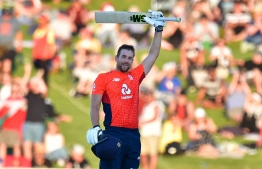 England's Dawid Malan celebrates 100 runs during the Twenty20 cricket match between New Zealand and England at McLean Park in Napier on November 8, 2019. (Photo by Marty MELVILLE / AFP)