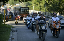 Electric motorcycle riders have come to the rescue of Cuban passengers delayed by fuel shortages. PHOTO: YAMIL LAGE / AFP