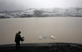 (FILES) This file photo taken on October 16, 2015 shows a cameraman taking pictures of the Solheimajokull glacier where the ice is retreating. - Each October since 2010, now-retired schoolteacher Jon Stefansson has brought students aged around 13 from a school in Hvolsvollur -- a village about 60 kilometres (35 miles) away -- to the glacier to record its evolution. The results are chilling: nestled between two moss-covered mountain slopes, Solheimajokull has shrunk by an average of 40 metres (130 feet) per year in the past decade, according to the students' measurements. (Photo by THIBAULT CAMUS / POOL / AFP)