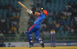 Afghanistan's Mohammad Nabi plays a shot during the third one day international (ODI) cricket match between Afghanistan and West Indies at the Ekana Cricket Stadium in Lucknow on November 11, 2019. (Photo by Rohit UMRAO / AFP) /