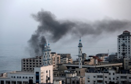 Smoke rises after an Israeli airstriked in Gaza City on November 13, 2019. - Israel's military killed a commander from Palestinian militant group Islamic Jihad in a strike on his home in the Gaza Strip, triggering exchanges of fire in a violent escalation that left another nine Gazans dead. (Photo by MAHMUD HAMS / AFP)