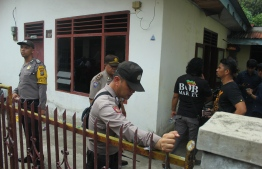 Indonesian police investigate a house where a suspected suicide bomber lives, in Medan, North Sumatra, on November 13, 2019, after a suspected suicide attack occured during their morning roll call. - A suspected suicide bombing outside a police station in Indonesia has left at least one attacker dead and six other people wounded, authorities said on November 13. (Photo by Rahmad SURYADI / AFP)