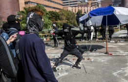 A protester unleashes an arrow while standing on a barricaded street outside The Hong Kong Polytechnic University in Hong Kong on November 15, 2019. - Pro-democracy protesters challenging China's rule of Hong Kong on November 14 choked the city for a fourth straight working day, firing arrows at police, barricading roads and disrupting transport links, as schools and businesses closed. (Photo by ISAAC LAWRENCE / AFP)