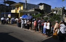 Voters queue up on a road near a polling station to cast their ballots during the country's presidential election in Colombo on November 16, 2019. - Sri Lankans voted on November 16 for a new president in what could mark a comeback for the Rajapaksa clan, lauded by supporters for crushing the Tamil Tigers but condemned by critics for war crimes, corruption and cosying up to China. (Photo by Lakruwan WANNIARACHCHI / AFP)