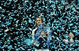 Greece's Stefanos Tsitsipas poses with the winner's trophy to after the men's singles final match on day eight of the ATP World Tour Finals tennis tournament at the O2 Arena in London on November 17, 2019. - Tsitsipas beat Austria's Dominic Thiem to win the match 6-7, 6-2, 7-6. (Photo by Glyn KIRK / AFP)