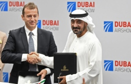 Ahmed bin Saeed Al Maktoum (R), CEO and chairman of the Emirates Group, and Guillaume Faury, Airbus CEO, pose for a picture after the signing of an agreement during the Dubai Airshow on November 18, 2019. - Emirates Airline said it will buy 50 Airbus 350-900 aircraft in a deal worth $16 billion, with delivery to begin from May 2023. (Photo by KARIM SAHIB / AFP)