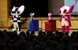 Tokyo 2020 Olympic and Paralympic Games' mascots and robot-type mascots Miraitowa (L) and Someity (R) attend a ceremony at Hoyonomori elementary school in Tokyo on November 18, 2019. Tokyo 2020 Summer Games' mascot robots visited an elementary school, drawing cheers and laughters from children as they gave them quizzes and responded to verbal instructions. Behrouz MEHRI / AFP