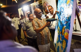 Mbongeni Buthelezi demonstrating his plastic painting method following the unveiling of the exhibition. PHOTO: COCO PALM BODU HITHI