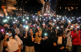 People hold their mobile phones as they gather to pray for the students who are barricaded inside Hong Kong Polytechnic University campus at Salisbury garden in Tsim Sha Tsui district of Hong Kong on November 19, 2019. - A dwindling number of exhausted pro-democracy protesters barricaded inside the Hong Kong university defied warnings on November 19 to surrender, as a police siege of the campus stretched through a third day and China sent fresh signals that its patience with nearly six months of unrest was running out. (Photo by YE AUNG THU / AFP)