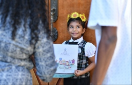 A pre-school student receives her report card on Thursday. PHOTO: HUSSAIN WAHEED / MIHAARU
