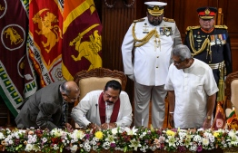 Sri Lanka's former president Mahinda Rajapaksa (C sitting) signs documents to take oath as country's Prime Minister while his brother, President Gotabaya Rajapaksa (R) looks on during the swearing-in ceremony in Colombo on November 21, 2019. - Newly elected Sri Lankan President Gotabaya Rajapaksa on November 20 named his brother Mahinda as Prime Minister, cementing the grip on power of a clan credited with brutally crushing the Tamil Tigers a decade ago. (Photo by LAKRUWAN WANNIARACHCHI / AFP)