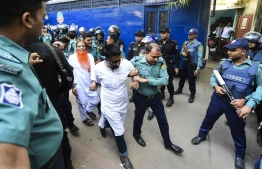Police escort detainees (C) accused of allegedly plotting the Holey Artisan Bakery cafe attack, carried out by Islamist militants, to a courtroom for their trial in Dhaka on November 27, 2019. - Five young men armed with guns and knives stormed the cafe on July 1, 2016 taking dozens hostage and killing 22 people. (Photo by Munir UZ ZAMAN / AFP)
