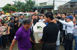 Crowds look on as relatives carry the casket bearing the body of Nguyen Van Hung arrives in Dien Chau district, Nghe An province on November 27, 2019 after being repatriated from Britain. - The first remains of the 39 people found dead in a truck in Britain last month arrived in Vietnam early November 27, capping a weeks-long wait by families eager to bury their loved ones. (Photo by Nhac NGUYEN / AFP)