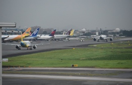 Passenger planes are parked while others taxi at the departure building of Manila international airport on December 3, 2019, hours before the deadline of the closure of the airport due to Typhoon Kamurri. - Typhoon Kammuri lashed the Philippines with fierce winds and heavy rain, as hundreds of thousands took refuge in shelters and the capital Manila prepared to shut down its international airport over safety concerns. (Photo by Ted ALJIBE / AFP)