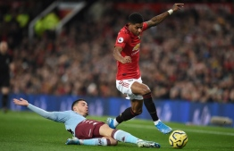 Aston Villa's French defender Frederic Guilbert (L) vies with Manchester United's English striker Marcus Rashford (R) during the English Premier League football match between Manchester United and Aston Villa at Old Trafford in Manchester, north west England, on December 1, 2019. (Photo by Oli SCARFF / AFP) / RESTRICTED TO EDITORIAL USE. No use with unauthorized audio, video, data, fixture lists, club/league logos or 'live' services. Online in-match use limited to 120 images. An additional 40 images may be used in extra time. No video emulation. Social media in-match use limited to 120 images. An additional 40 images may be used in extra time. No use in betting publications, games or single club/league/player publications. /