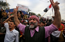 Iraqi demonstrators shout slogans as thee take part in an anti-government demonstration in the capital Baghdad's Tahrir Square, on December 6, 2019. - Tahrir has become a melting pot of Iraqi society, occupied day and night by thousands of demonstrators angry with the political system in place since the aftermath of the US-led invasion of 2003 and Iran's role in propping it up. (Photo by AHMAD AL-RUBAYE / AFP)