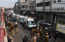 Police personnel and ambulances are seen  along a road following a factory fire in Anaj Mandi area of New Delhi on December 8, 2019. - At least 43 people have died in a factory fire in India's capital New Delhi, with the toll still expected to rise, police told AFP on December 8. The blaze broke out in the early hours in the city's old quarter, whose narrow and congested lanes are lined with many small manufacturing and storage units. (Photo by Sajjad  HUSSAIN / AFP)