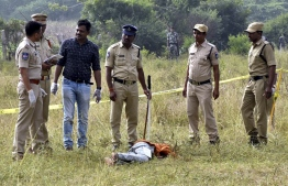 Police personnel stand next to the body of a man at the site where Police officers shot dead four detained gang-rape and murder suspects in Shadnagar, some 55 kilometres (34 miles) from Hyderabad, on December 6, 2019. - Indian police on December 6 shot dead four detained gang-rape and murder suspects as they were re-enacting their alleged crime, prompting celebrations but also accusations of extrajudicial killings.  The men, who had been in custody for a week over the latest gruesome case of violence against women to shock India, were shot in the early morning as they tried to escape during the staged re-enactment in Hyderabad, police said. (Photo by STR / AFP)