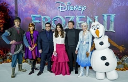 """In this file photo taken on November 17, 2019 US actor Josh Gad (3rd L), US actor Idina Menzel (C) and US actor Jonathan Groff (3rd R) pose with people dressed as characters from the film on the red carpet as they arrive to attend the European premiere of the film """"Frozen 2"""" in London. - In a rare show of box-office stasis, the top five films in North American theaters were unchanged this weekend from last, led again by Disney blockbuster """"Frozen 2,"""" industry watcher Exhibitor Relations said Sunday. (Photo by Niklas HALLE'N / AFP)"""