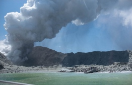 This handout photograph courtesy of Michael Schade shows the volcano on New Zealand's White Island spewing steam and ash minutes following an eruption on December 9, 2019. - New Zealand police said at least one person was killed and more fatalities were likely, after an island volcano popular with tourists erupted on December 9 leaving dozens stranded. (Photo by Handout / Michael Schade / AFP)