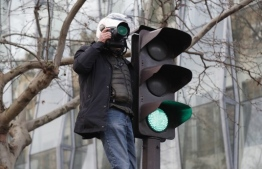 A journalist standing on a traffic sign takes pictures during a march in Paris on December 10, 2019 on a sixth day of a strike of public transport operators SNCF and RATP employees over French government's plan to overhaul the country's retirement system. - Unions have vowed to keep up the fight over the reforms, which are set to be finalised and published on December 11. Another mass demonstration is planned in Paris and other cities today, with teachers and other workers once again expected to walk out alongside transport workers. (Photo by Zakaria ABDELKAFI / AFP)