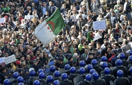 Algerian security surround protesters during an anti-government demonstration in the capital Algiers on December 11, 2019, ahead of the presidential vote scheduled for December 12. - Algeria's contentious presidential election campaign is highlighting the vast gap between youth at the heart of a reformist protest movement and an ageing elite they see as clinging to power. The poll will see five candidates, all linked to ex-president Abdelaziz Bouteflika, compete for the top office. But protesters, whose mass mobilisation forced the ex-strongman to resign from his two-decade tenure in April, have rallied weekly to say sweeping reforms must come ahead of any vote. (Photo by RYAD KRAMDI / AFP)