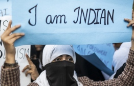 Protesters display placards during a demonstration against the Indian government's Citizenship Amendment Bill in New Delhi on December 14, 2019. - Protests against a divisive new citizenship law raged on December 14 as Washington and London issued travel warnings for northeast India following days of violent clashes that have killed two people so far. (Photo by Jewel SAMAD / AFP)