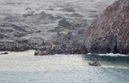 """This handout photo taken and released on December 13, 2019 by the New Zealand Defence Force shows elite soldiers taking part in a mission to retrieve bodies from White Island after the December 9 volcanic eruption, off the coast from Whakatane on the North Island. - Elite soldiers retrieved six bodies from New Zealand's volatile White Island volcano on December 13, winning praise for their """"courageous"""" mission carried out under the threat of another eruption. (Photo by Handout / NEW ZEALAND DEFENCE FORCE / AFP) /"""