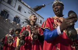 """A Gnawa traditional group performs in the city of Essaouira on December 14, 2019, to celebrate the decision of adding the Gnawa culture to UNESCO's list of Intangible Cultural Heritage of Humanity. - Gnawa culture, a centuries-old Moroccan practice rooted in music, African rituals and Sufi traditions, was added to UNESCO's list of Intangible Cultural Heritage of Humanity earlier in the week. Gnawa refers to a """"set of musical productions, fraternal practices and therapeutic rituals where the secular mixes with the sacred"""", according to the nomination submitted by Morocco. Often dressed in colourful outfits, Gnawa musicians play the guenbri, a type of lute with three strings, accompanied by steel castanets called krakebs. (Photo by FADEL SENNA / AFP)"""