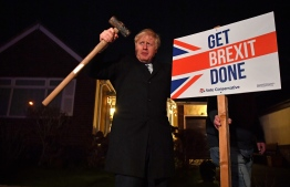 "Britain's Prime Minister and Conservative party leader Boris Johnson poses after hammering a ""Get Brexit Done"" sign into the garden of a supporter, with a sledgehammer as he campaigns with his team in Benfleet, east of London on December 11, 2019, the final day of campaigning for the general election. - Britain will go to the polls tomorrow to vote in a pre-Christmas general election. (Photo by Ben STANSALL / POOL / AFP)"
