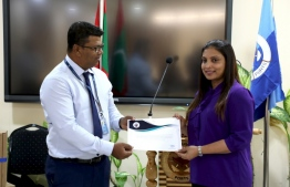 MPL's Chief Executive Officer Shahid Ali (L) presents 10 computer systems,gifted by MPL to the education ministry, to Minister Dr Aishath Ali. PHOTO/MPL