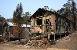 """This photo taken on January 11, 2020 shows accommodation blocks at the Gold Rush Colony in Mogo, a tourist attraction dedicated to Mogo's 1850s gold rush -- where a recent bushfire reduced it to twisted metal and ash. - The unprecedented scale Australia's summer's bushfires have tainted the country's reputation as a safe and alluring holiday destination. Thousands of tourists were evacuated from coastal towns, international visitors have cancelled flights, and the US State Department even upgraded its security advice for Australia -- warning travellers to """"exercise increased caution"""" due to the bushfire risk. (Photo by PETER PARKS / AFP) /"""