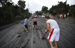 "Residents help scrape a road covered wih mud spewed by Taal volcano over Tanauan town, Batangas province south of Manila on January 13, 2020. - Lava and broad columns of ash illuminated by lightning shot from an erupting volcano south of the Philippine capital on January 13, grounding hundreds of flights amid an alert for a possible ""explosive eruption"". (Photo by Ted ALJIBE / AFP)"