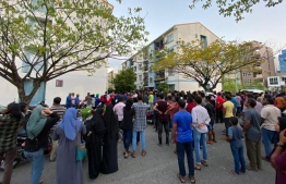 Dozens of people gathered and broke the window of a flat in reclaimed suburb Hulhumale' on Friday, where the father of the sexually abused two-year-old child is said to reside.