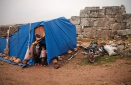 Syrian children, displaced from the western countryside of Aleppo province, stand through the doorway of a tent at the site of ancient ruins where they are encamped for refuge from the rain near the town of Atareb on January 19, 2020. (Photo by Aaref WATAD / AFP)