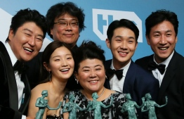 """Parasite"" cast (L-R) Song Kang-ho, Cho Yeo-jeong, director Bong Joon-ho, Lee Jung-eun, Choi Woo-shik, and Lee Sun-kyun pose with the trophy for Outstanding Performance by a Cast in a Motion Picture in the press room during the 26th Annual Screen Actors Guild Awards at the Shrine Auditorium in Los Angeles on January 19, 2020. (Photo by Jean-Baptiste Lacroix / AFP)"