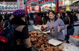 A vendor (R) sells meat at a market in Beijing on January 15, 2020. - China's trade surplus with the United States narrowed last year as the world's two biggest economies exchanged punitive tariffs in a bruising trade war, official data showed. (Photo by NICOLAS ASFOURI / AFP)