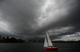 """Storm clouds gather over Sydney Harbour on January 20, 2020. - Thunderstorms and giant hail battered parts of Australia's east coast after """"apocalyptic"""" dust storms swept across drought-stricken areas, as extreme weather patterns collided in the bushfire-fatigued country. (Photo by PETER PARKS / AFP)"""