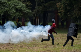A Protestor runs carrying a tear gas cannister during clashes with Colombian riot police in a demonstration against the government of Colombia's President Ivan Duque in Cali, on January 21, 2020. Colombians reactivated the protests against the government with marches and roadblocks in cities such as Bogota, where clashes occurred, where clashes broke out with at least four injured and several detainees. Luis ROBAYO / AFP